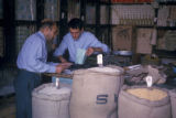 Tehran (Iran), two men look at paperwork in shop
