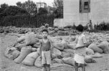 Shanghai (China), children playing among sandbags