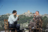 Burj Safita (Syria), two men having tea with city in the background