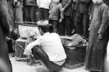 China, people gathered around man with performing monkey