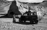 China, Harrison Forman standing next to truck in mountains