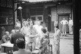 China, Harrison Forman shaking hands with woman in Japanese-style dress