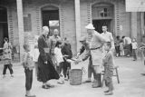 Xuzhou (China), Harrison Forman and Bishop Philip Cote watching food being distributed to refugees