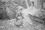 China, child collecting rocks in a basket