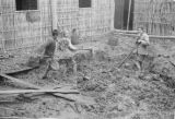 China, children mixing mud to apply on lath walls for building construction