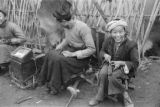 China, one of several images of a boy and man making or repairing shoes