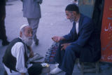 Tehran (Iran), two seated men talking on city street