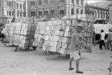 Shanghai (China), man standing in front of carts with tin containers