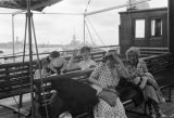 Shanghai (China), evacuees sitting on boat deck with warships in background