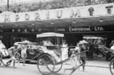 Victoria (China), automobiles and rickshaws moving past China Emporium