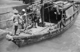 Hong Kong (China), men and children on sampan docked at pier