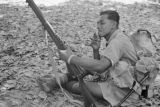 Malaysia, soldier smoking and looking at rifle during the Malayan Emergency