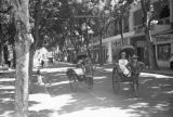 Indochina, people riding rickshaws on commercial street