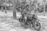 Malaysia, soldiers riding camouflaged motorcycle in jungle