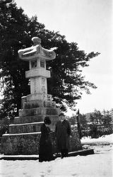 Kamakura (Japan), people near old stone lantern in snowy landscape