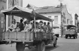Singapore, military men riding in covered truck in business district