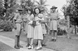 Singapore, Asian women in Western style dresses standing with men in uniform