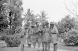 Singapore, Harrison Forman showing his camera to group men in uniforms