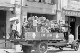 Singapore, men loading bundled sheets of rubber for delivery