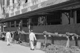 Singapore, men constructing brick wall barricade in front of building