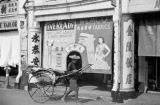 Singapore, rickshaw and driver in front of shop with battery and fabric signs