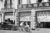 Singapore, man bicycling in front of store selling writing goods