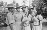 Singapore, women talking with group of uniformed men