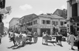 Singapore, street scene with oxen-drawn carts and shops in business district