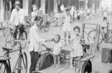 Singapore, woman feeding infant child standing in three wheel bicycle