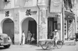 Singapore, man riding three-wheeled bicycle past shops on Synagogue Street