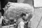 Singapore, man carrying bale of rubber sheets to load on truck