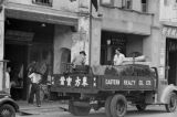 Singapore, men loading bales of rubber sheets on truck for shipment