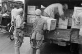 Shanghai (China), armed soldiers loading crates onto truck