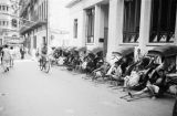 Hong Kong (China), rickshaws and drivers lined up along building