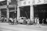 Hong Kong (China), street scene with ships and boys walking with poles