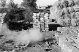 Gansu province (China), smoke coming from ground near stacked roofing tiles and bricks