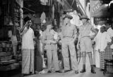 Singapore, uniformed men in street market