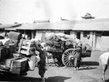 Huainian (China), men loading carts in front of Inn