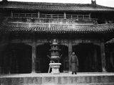 Duolun (China), man standing in front of temple next to three-legged urn