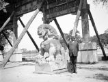 Beijing (China), Western man standing next to guardian lion sculpture in Beihai Park