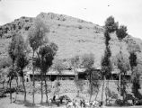 China, caravan resting below temple in mountainside