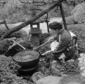 Japan, woman with wooden scoop at fountain in garden