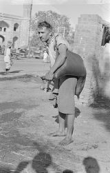 Pakistan, man carrying animal skin bag on shoulder in Lahore