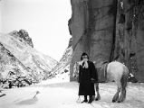 China, man with horse on snow covered mountain pass