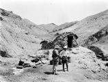 Iran, men standing before benzene well enclosed by rock wall