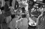 Pakistan, children surrounding food vendor on street in Karāchi