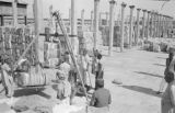 Pakistan, men weighing bale of cotton on platform in Karāchi