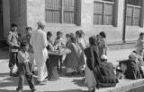 Pakistan, man selling sweets to children before A. U. Islamia High School in Karāchi