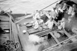 Hong Kong, woman cooking on houseboat docked at pier