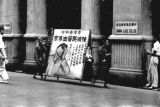 Hong Kong, men carrying advertisement for health clinic past China Lace Co. Ltd.